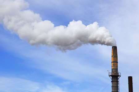 Old factory smoke stack billowing a white gray plume across blue and white cloud sky photo