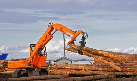 pile engine: Heavy duty orange claw like logging machine for picking up and piling logs with river and ship in background