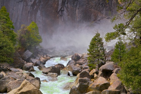Green flowing river over large rocks and boulders with mist and rock cliff in background photo