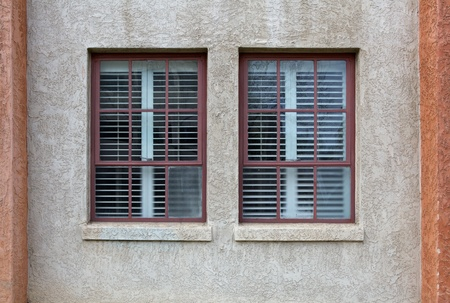 Two maroon bordered windows on a stucco wall Stock Photo - 9258185