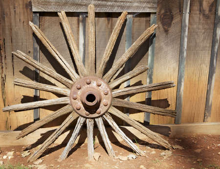 Broken Wagonwheel with rim missing in strong sunlight against a barn wall photo