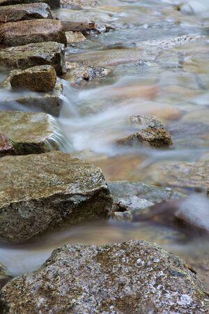 Rij van stepping stones over een bergbeek