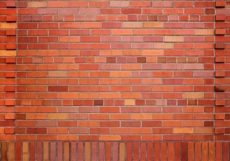 붉은 색과 오렌지색과 디자인 된 테두리의 다른 그늘이있는 새로운 붉은 벽돌 벽
