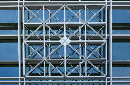 Intersection bars of metal in a geometric pattern in from of a glass wall
