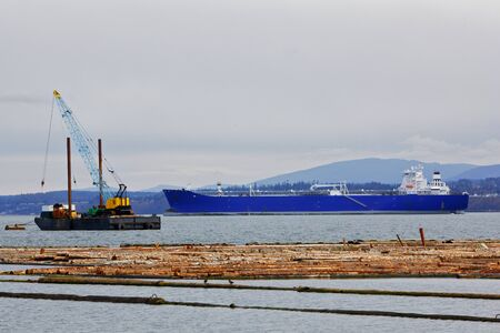Scene of frieghter or tanker shipping and the lumber industry at Port Angeles WA on a cloudy day photo