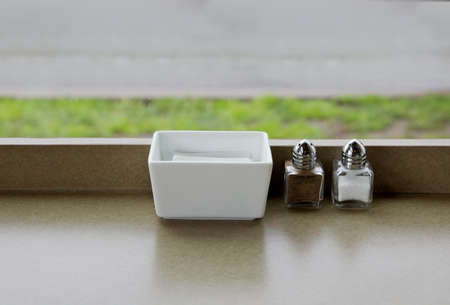 Simple salt and pepper shaker with sugar dish on a restaurant countertop with soft focus grass and road view in background photo