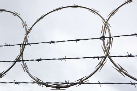 Nasty Looking circular Barbed Wire on tradional horizontal fence with gray sky background Banco de Imagens
