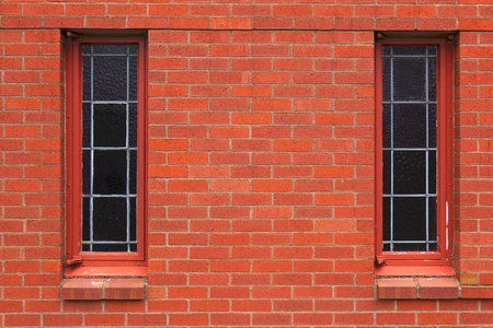 Two narrow leaded windows in a red brick wall church photo
