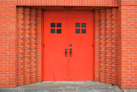 Two red metal doors recessed in brick wall of church photo