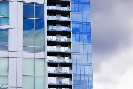 Three office and apartment buildings staggered in their view against a cloudy sky photo