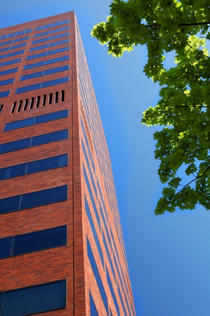 contemporary: Tall red brick business building with dark windows bordered by blue sky and green trees Stock Photo