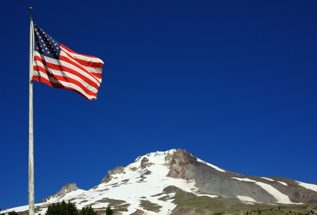 An American Flag flying with Mount Hood in the background with a deep blue sky
