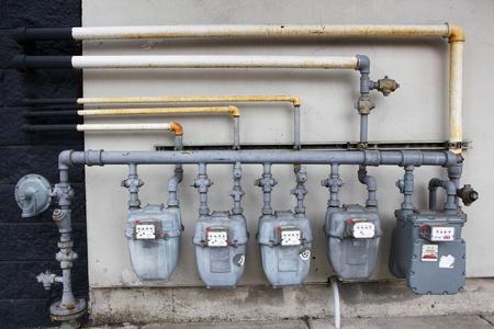 Cinq compteurs de gaz gris contre un mur noir et blanc Banque d'images - 10554792