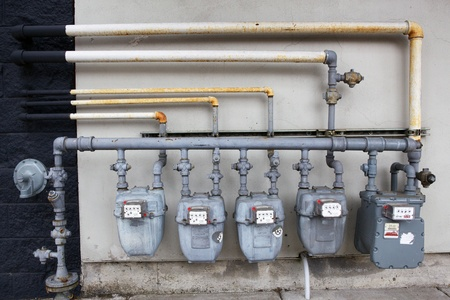 Five gray gas meters against a black and white wall Stock Photo