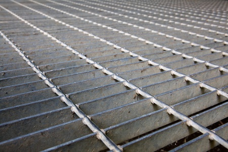 Gray steel grating image taken low to the ground for a long diminished perspective Stock Photo