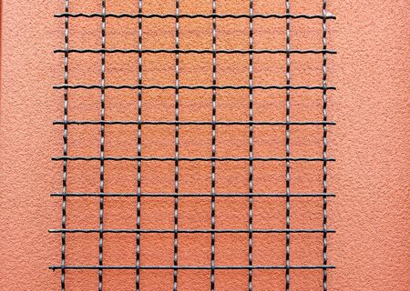 Black wire grid against a salmon stucco wall Stock Photo - 10554796