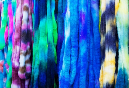 Blue, violet, yellow, green, and white strands of un-woven yarn
