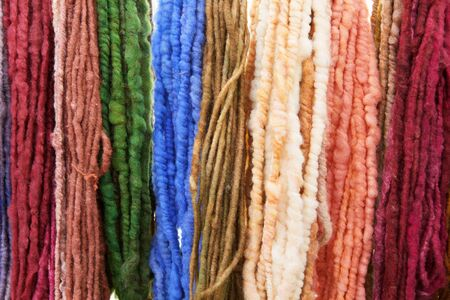 Wall of many colors of raw yarn for sale photo