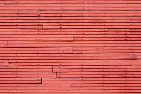 Old wood slat wall painted red with vertical nail holes photo