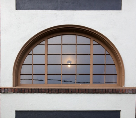 semicircular: Old style multi paned window with circular shapeon white stucco building Stock Photo