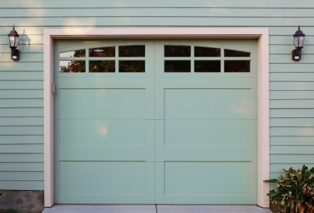 Light green garage door with windows and two lanterns photo