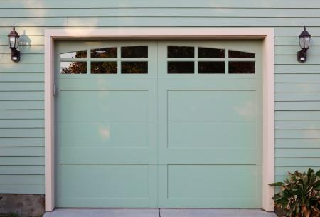 garage: Light green garage door with windows and two lanterns Stock Photo