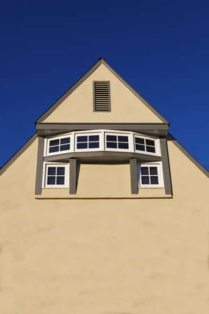Unique rotunda windows on large beige home wall with dark blue sky Stock Photo - 11882245