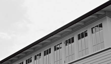 Long row of window below a roof on cloudy day in black and white photo