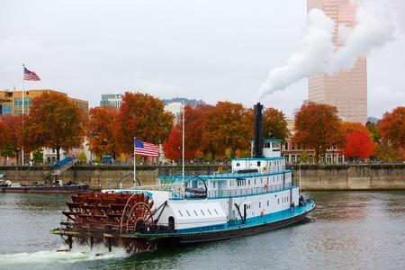 曇りの日に 2 つのアメリカの旗を持つ蒸気下 Williamette 川にポートランドのフェリーまたは蒸気のボート 写真素材