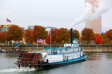 Ferry or steam boat in Portland on Williamette river under steam with two American flags on an overcast day