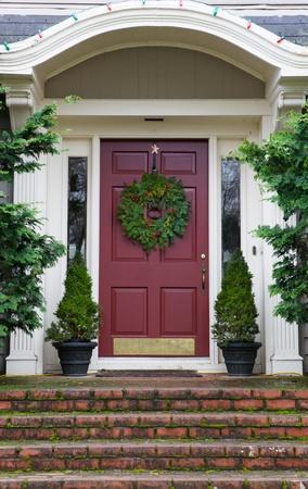 灰色の苔の赤レンガの手順と一緒に家に花輪を捧げるとマゼンタのドア