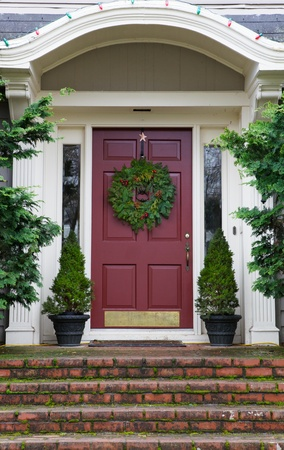 front of house: Magenta Door with Wreath on gray home with mossy red brick steps