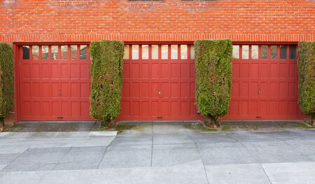 Three Red Garages on a brick wall separaged by evergreen bushes Stock Photo - 12686683