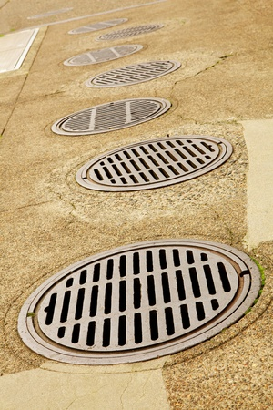sink drain: Uneven Line up of Sewer Drains on a sidewalk Stock Photo