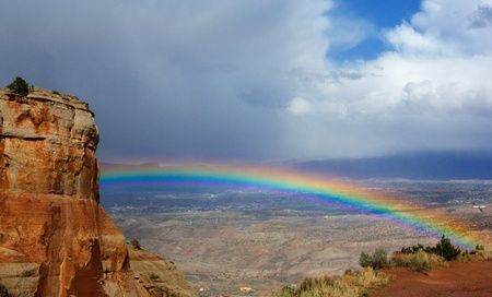 utah: Bright rainbow over Grand Junction  Colorado from National Monument Park Stock Photo