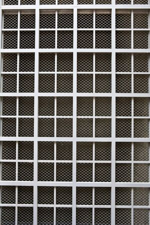 perforated: Dull silver color metal bars over screen covering building window