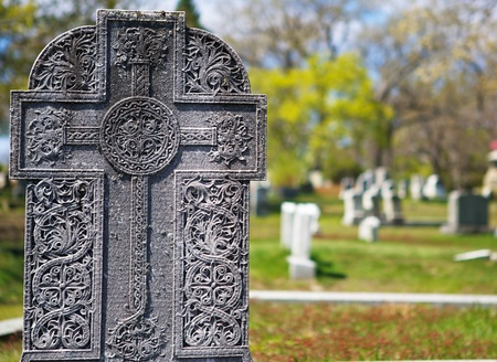 ornately: Older worn ornately engraved Celtic design on Cemetary grave stone with soft focus background Stock Photo