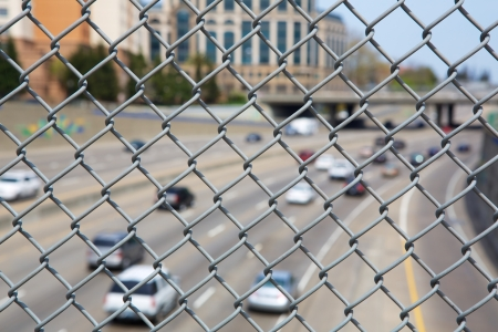 Narrow Dept of Field close up image of chain link fence with out of focus highway and cars photo