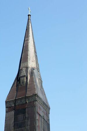 Curious black net shrouded Christian church steeple against blue sky photo