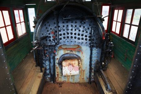 Old train engine steam boiler that is old, worn down, and rusted