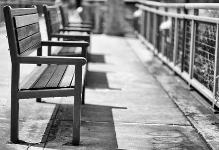 Green wood and metal Benches with closest in shallow focus trailing to softer background