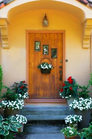 Porte de maison tachée de bois patiné avec trois fenêtres et des fleurs Banque d'images - 15988322