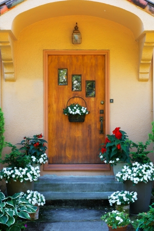front of house: Weathered wood stained home door with three windows and flowers Stock Photo