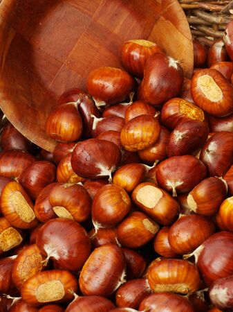 Wooden bowl scooping up chestnuts in a basket