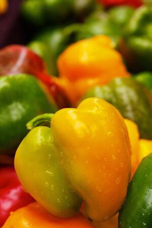 Green and Yellow Bell Peppers at the farmers market with sharp focus on center vegetable photo