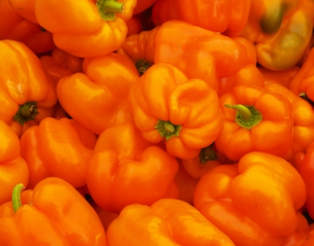 Orange Bell Peppers at the farmers market with sharp focus on center vegetable