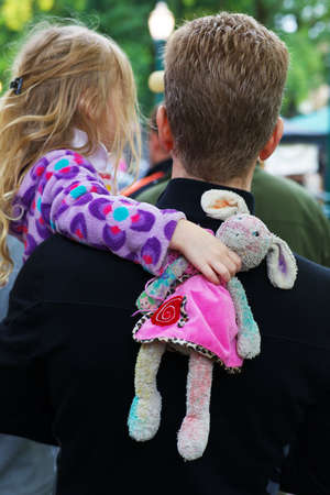 Back view of standing Father holding daughter while she holds her stuffed doll
