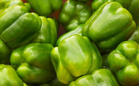 Green Bell Peppers at the farmers market with sharp focus on center vegetables photo