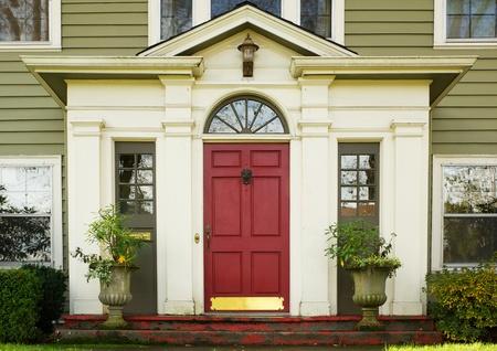 2 つの大きく鉢植えな植物によって接されるマゼンタ ホーム ドア 報道画像