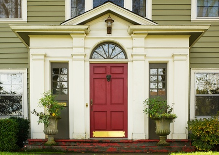 front of: Magenta Home door bordered by two large potted plants